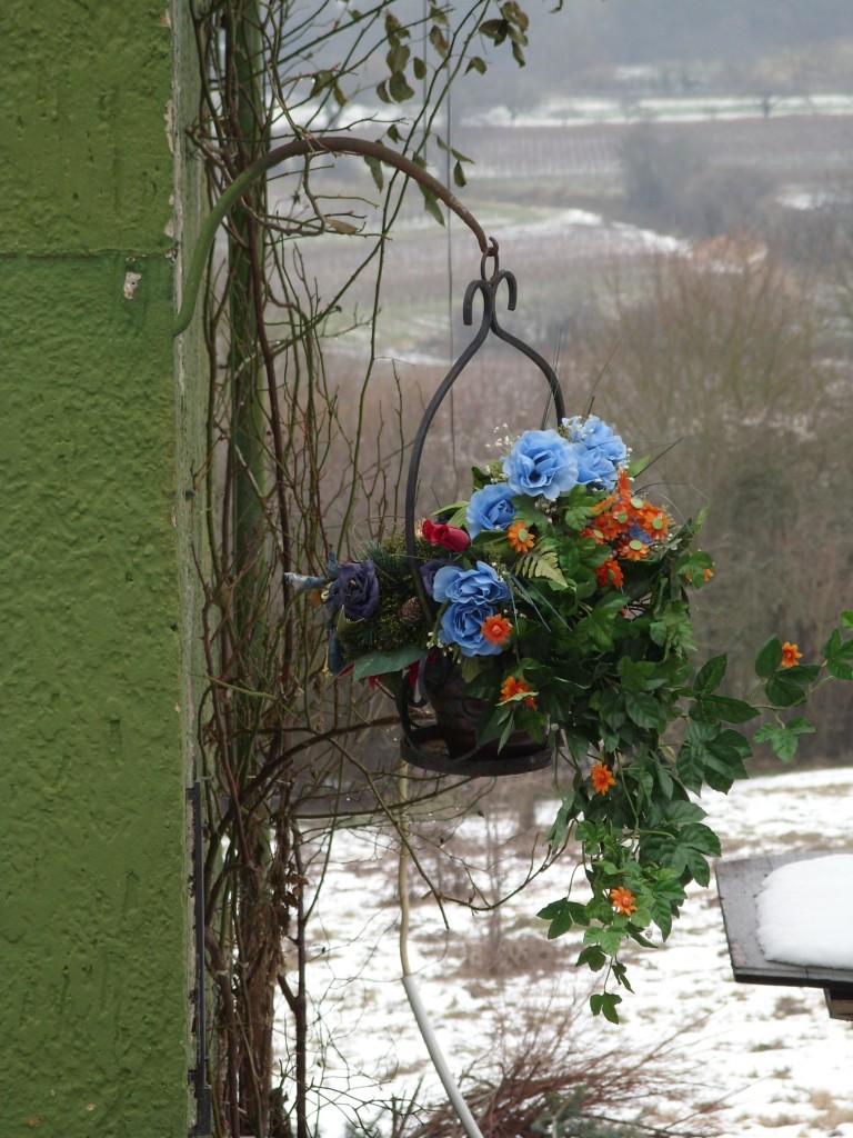 Blühendes Plastik an verlassem Haus in Februarlandschaft - ein interessanter Geschmack